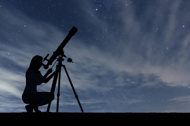 Girl looking at the stars with telescope. Starry night sky